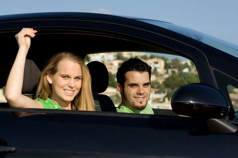 Couple on road trip in new or hire rental car