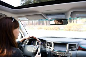 young_woman_looking_rear_view_mirror